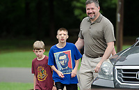 "Michael McCollum<br /> 8/2/18<br /> David Overman arrives with his sons Ryan,13,(middle) and Alex,7, at the reveal ceremony where it was announced to Ryan Overman of west Knoxville that The Wish Connection is granting Ryan's wish to go to Washington DC and visit the White House at Carl Cowan Park, 10058 S Northshore Dr, Knoxville, TN , Thursday, August 2, 2018 at 5:45pm. Approximately 50-60 people attended, including the Overman family, friends, and AT&T Employees. The Bearden High School Cadets also attended and lead the pledge of allegiance.<br />  The AT&T Wish Connection is going to send Ryan, his family, and his service dog to Washington DC and while they are gone, the group of volunteers will be doing a makeover on his bedroom and turn it into the ""Oval Office"" at the White House.<br /> Ryan was born two weeks prematurely on May 13, 2005.  During the pregnancy he was classified as high risk due to a measured lack of growth and, after a brief stay in the hospital, he came home weighing only 4 lbs 5 oz.  His development was much slower compared to his peers, such as not learning to walk until he was well over a year old, and he was much smaller. The Overman family worked with Tennessee Early Intervention Services (TEIS) when Ryan was about one year old and with their help they were able to get Ryan enrolled through TEIS to receive Occupational, Physical, and Speech Therapy.  When Ryan turned three he transitioned from TEIS to the Knox County Early Intervention Program and began attending a special school to continue his therapies until he was old enough to enroll at Cedar Bluff Elementary and now is at Cedar Bluff Middle School. In 2016, Ryan was diagnosed to have retinitis pigmentosa, a degenerative disease of the retinas that under the best of circumstances causes severe tunnel vision, but more commonly results in complete blindness.<br />  Despite the physical difficulties that Ryan has had to endure over the last thirteen years, he continually brightens the lives of those around"