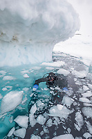 underwater photographer, Franco Banfi, at the surface, ready to dive under the iceberg, Tasiilaq, Greenland, North Atlantic Ocean