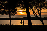 Hand in hand, a couple walks along the path at the San Leandro Marina Park at sunset on a winter evening.