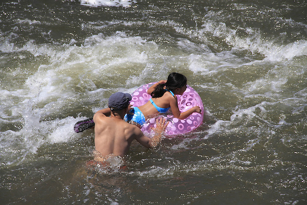 Father and daughter with inner tube in Confluence Park, Denver, Colorado, USA.