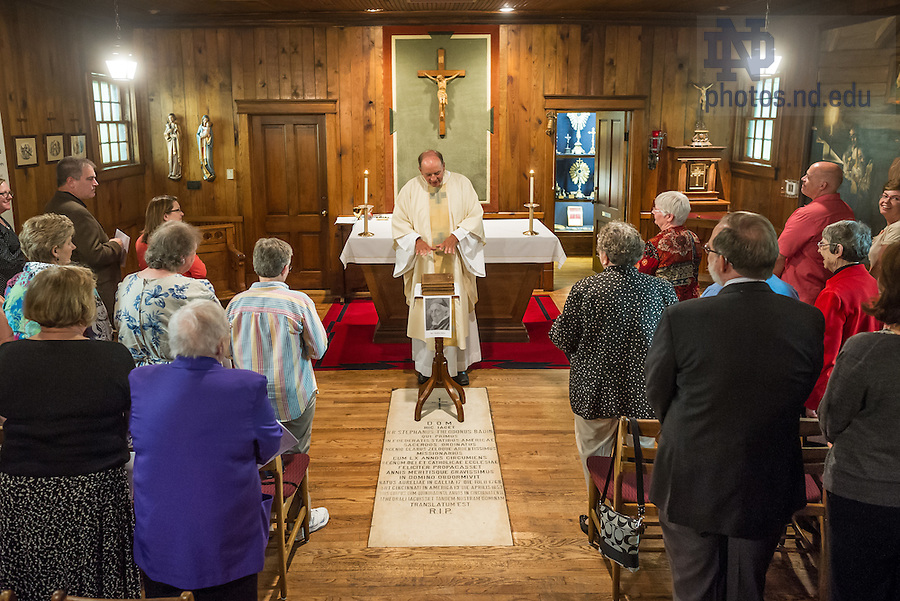 Jul. 14, 2014; Rev. Peter Rocca, C.S.C. gestures toward the three volumes of a bible once owned by Rev. Stephen Badin during a Mass in the Log Chapel where Father Badin is buried.  Father Badin's Bible was purchased from the Sisters of Loretto of Nerinx, Kentucky, and a delegation of sisters was present at the Mass.<br /> <br /> Photo by Matt Cashore/University of Notre Dame