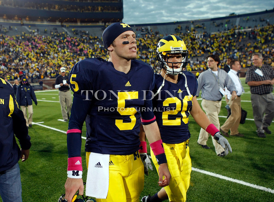 Michigan quarterback Tate Forcier (5) and safety Ray Vinopal (20) walk off the Michigan Stadium field after an NCAA college football game with Iowa, Saturday, Oct. 16, 2010, in Ann Arbor, Mich. Iowa won 38-28. (AP Photo/Tony Ding)