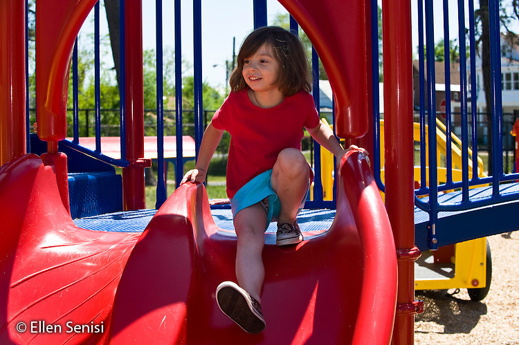 MR / Schenectady, New York. Fulton Early Childhood Education Center (urban public school early childhood education center). Pre-K classroom. Student (girl, 5) ready to go down slide on playground at recess. ID: AI-gPd. MR: Sto6 ©Ellen B. Senisi