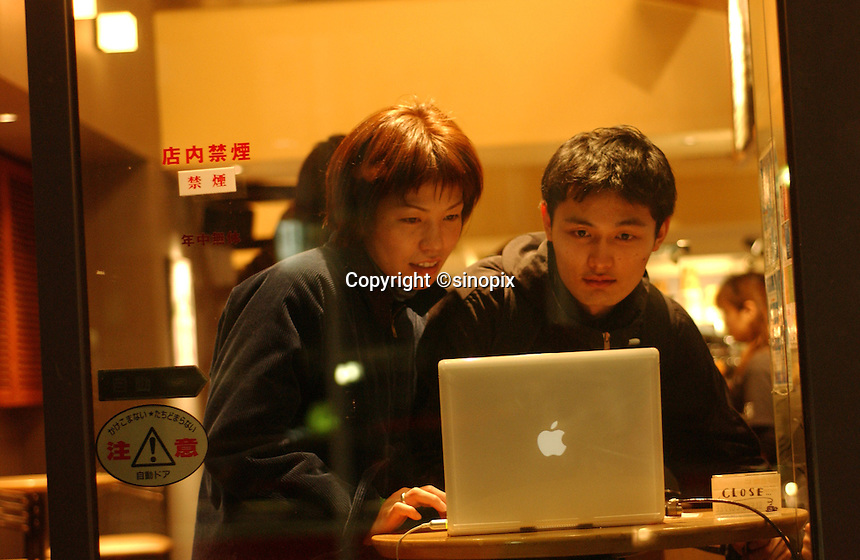 A young couple use an Apple computer in a coffee shop in Tokyo, Japan. Most coffee shops offer outlets to plug-in portable computers..Mar 2002