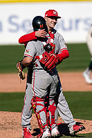 Freshman pitcher Jason Savacool (45) of the Maryland Terrapins, making his collegiate debut, pitched a complete-game 3-2 win against the Michigan State Spartans on Sunday, March 7, 2021, at Fluor Field at the West End in Greenville, South Carolina. Here he hugs catcher Luke Shliger (27) after the final out. (Tom Priddy/Four Seam Images)