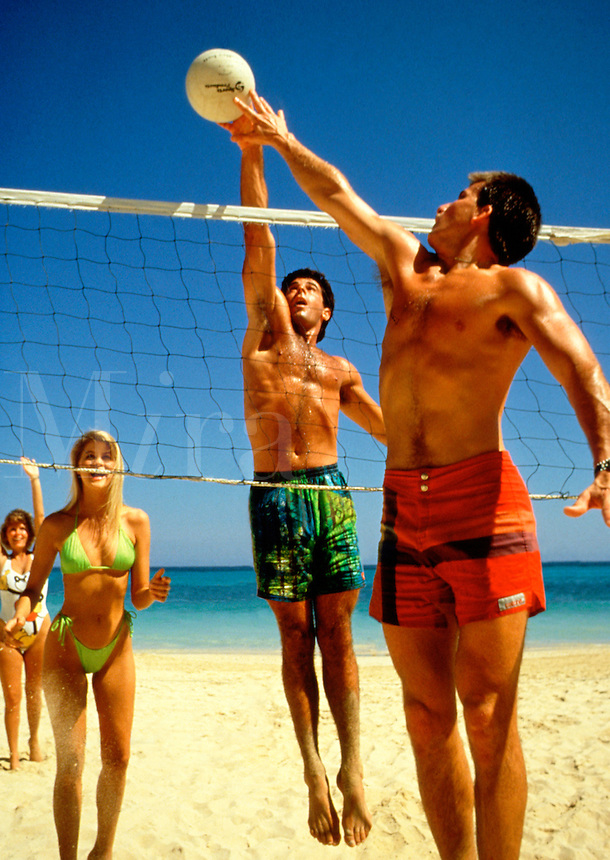Couples playing volleyball on the beach