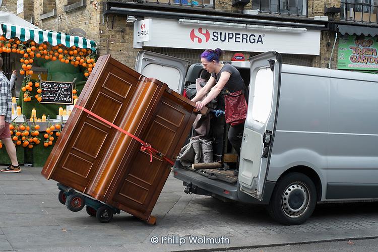 Young woman loading a piano into a van, camden Town, London.