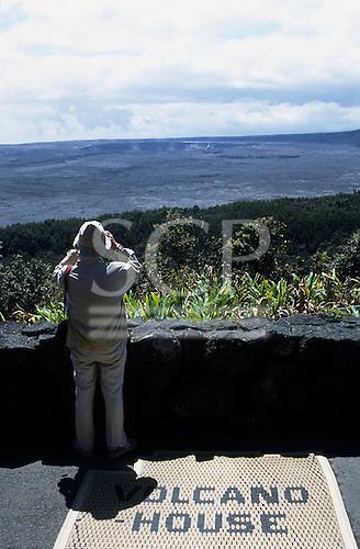 Kona Island, Hawaii, USA. Tourist with binoculars looking over the Kilauea volcano crater on a mat 'Volcano House'.