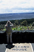 Kona Island, Hawaii, USA. Tourist with binoculars looking over the Kilauea volcano crater on a mat 'Volcano House'.