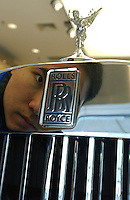 A man looking at a Rolls-Royce in a show room in Shanghai, China..