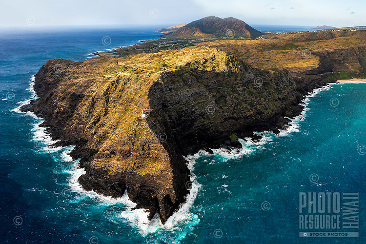 A helicopter view of the seemingly tiny red and white Makapu'u Lighthouse at Makapu'u Point, with Koko Crater in the distance, East O'ahu.