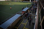 Prescot Cables 2 Brighouse Town 1, 13/02/2016. Hope Street, Northern Premier League. Spectators in the enclosure watching the first-half action as Prescot Cables (in orange) take on Brighouse Town in a Northern Premier League division one north fixture at Valerie Park. Founded in 1884, the 'Cables' in their name came from the largest local employer, British Insulated Cables and they have played in their current ground, also known as Hope Street, since 1906. Prescott won the match 2-1 watched by a crowd of 189. Photo by Colin McPherson.