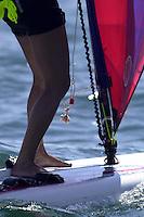 A sailboarder rides along the ocean.