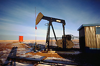 Oil Well Nodding Donkey, or Pump Jack, pumping in the Oil Field north of Dawson Creek, Northern British Columbia, Canada
