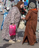 Marrakesh, Morocco.  Two Women Talking in the Place Jemaa El Fna.