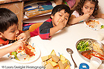 Preschool Headstart 3-5 year olds meal lunch time children eating spagetti pasta tomato sauce and vegetable broccoli horizontal