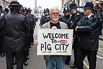 """© Joel Goodman - 07973 332324 . 30/06/2011 . London , UK . A protester with a placard reading """" Welcome to Pig City """" adjascent to police on Whitehall . Tens of thousands of public sector workers demonstrate and march through the City of London in protest at proposed changes to their pensions . Photo credit : Joel Goodman"""