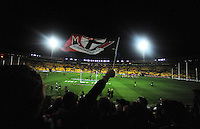 A fan waves a St Kilda flag from the grandstand during the ANZAC Day AFL match between St Kilda Saints and Brisbane Lions at Westpac Stadium, Wellington, New Zealand on Friday, 25 April 2014. Photo: Dave Lintott / lintottphoto.co.nz