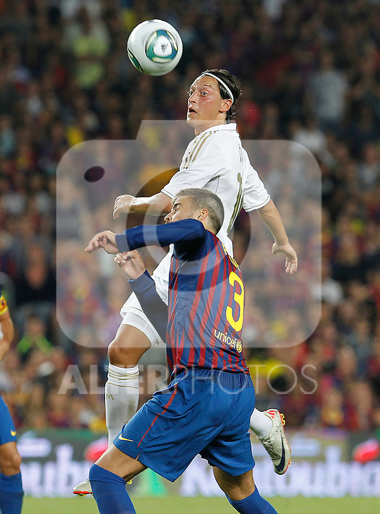 FC Barcelona's Gerard Pique (d) and Real Madrid's Mesut Ozil during Spanish Supercup 2nd match.August 17,2011. (ALTERPHOTOS/Acero)
