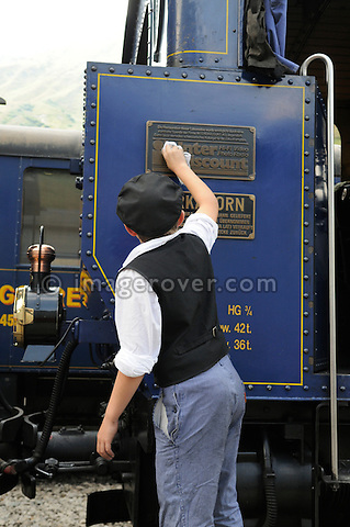 Boy polishing the Furka cogwheel steam railway engine at Realp station. Switzerland, Western Europe, Grimsel-/Furka region, Uri.  The steam engine HG 3/4 No. 1 Furkahorn DFB 1 was built in 1913. With an engine power of 600 hp and a weight of 42 tons it manages a maximum speed of 45 km/h on adhesion rails and 20 km/h on cogwheel rails. Note: No releases available. --- Info: In 1914 the first steam trains started from Brig and reached Gletsch traveling along the river Rhone. In the following years the line was extended and finally connected in Disentis with the Rhätische Bahn in 1926. Although the Furka-Oberalp-Bahn was electrified in 1942, due to the extreme climate and the topography of this alpine area the trains could not run between Oberwald and Realp through the winter. So in the 1970's a modern tunnel was built for all year use. In 1983 the Furka Cogwheel Steam Railway Club was founded by railway enthusiasts to repair and maintain the original track and rolling stock. This included bringing back and restoring the original steam engines that were sold of to Vietnam in 1947. In late summer 2010 the historic steam link over the Furkapass was finally fully reestablished!