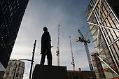 The Monument to an Unknown Artist, an animatronic sculpture by the public art collective Greyworld, looks over a new development in Southwark, London.  Sale prices for flats in Neo Bankside range from £1m to £6.5m.  A Latin inscription on the monument translates as: Don't applaud, throw money.