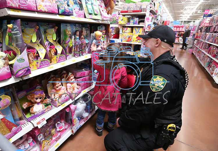 CCSO Dep. Dan Jones helps a young shopper pick a doll at the 10th annual Holiday with a Hero event at Walmart in Carson City, Nev., on Wednesday, Dec. 17, 2014. The event pairs 200 of Carson City's K-5th grade homeless students with a local heroes for Christmas shopping. <br /> Photo by Cathleen Allison