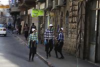 Niños Haredis vistiendo barbijos caminan por el vacío  barrio ultraortodoxo Mea Shearim. En un esfuerzo por detener el contagio del COVID 19 el gobierno israelí decreto el uso obligatorio de barbijos en las calles. La pandemia ha afectado fuertemente a la comunidad Haredi. El gobierno israelí decreto un confinamiento limitando la salida a 100 metros de los hogares. <br /> Foto Quique Kierszenbaum