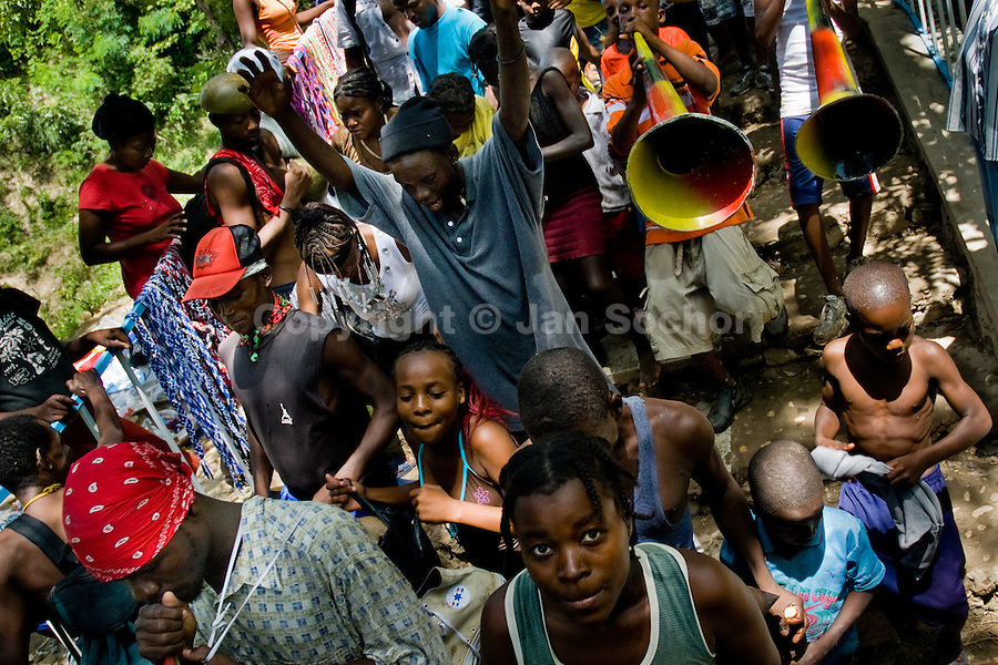 Haitian pilgrims, both followers of Catholicism and Voodoo, dance and sing during the annual religious pilgrimage in Saut d'Eau, Haiti, July 16, 2008. Every year in summer thousands of pilgrims from all over Haiti make the religious journey to the Saut d'Eau waterfall (100km north of Port-au-Prince). It is believed that 150 years ago the spirit of Virgin Mary (Our Lady of Mount Carmel) has appeared on a palm tree close to the waterfall. This place became a main pilgrimage site in Haiti since then. Haitians wearing only underwear perform a bathing and cleaning ritual under the 100-foot-high waterfall. Voodoo followers (many Haitians practise both voodoo and catholicism) hope that Erzulie Dantor, the Voodoo spirit of water, manifest itself and they get possessed for a short moment, touched by her presence.