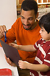 Preschool 3-4 year olds male teacher looking at and talking about student work or something on paper with boy vertical