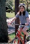 10 year old girl on bicycle wearing safety helmet full length Caucasian vertical