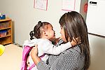 Education preschool first days of school 2-3 year olds sad girl clinging to mother at start of school day