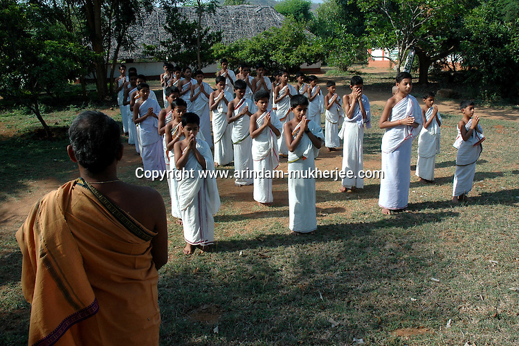 Students at Om Shantidhama during the early morning prayer. Om Shantidhama is a residential vedic school for boys. Nestled among the confluence of hills, forest and rivers - Om Shanti Dhama is a world removed from the maddeningly fast and often chaotic urban India. Students from allover the country are selected to take part in its Vedic and free education system. What is unique about this institute is that they have blended the traditional and modern education system. Here computer and science is taught with the same passion as the Vedas and Shastras, helping the students to grow spiritually as well as earn a living. Bonding with the nature and animal world is a mandatory part of the institute's curriculum. Karnataka, India. Arindam Mukherjee