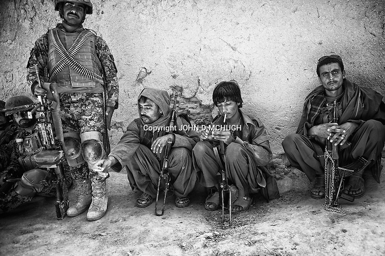 Abdul Jalil, an Afghan Local Police commander, is seen (3L) alongside other ALP during a short lull in a five hour firefight with the Taliban in Pay-E Moluk village, Panjwayi district, Kandahar, 30 April 2013. Jalil was killed fighting the Taliban days after this photo was taken. (John D McHugh)