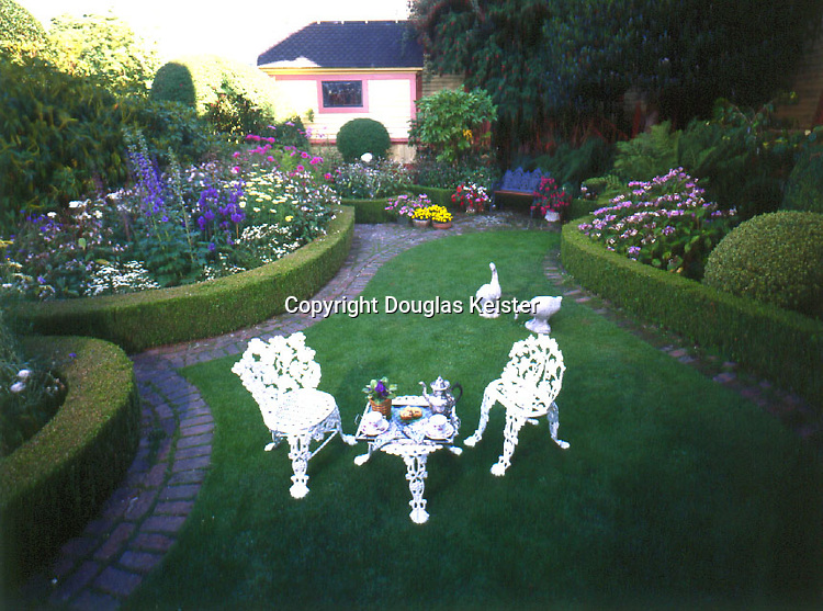 The courtyard of the Gingerbread Mansion bed and breakfast, in Ferndale, California, plays host to leisurely breakfasts and afternoon teas. The flowery cast-iron furniture is in the effervescent Victorian style, just like the gingerbread on the house. The garden is planted with lush hydrangeas on the right and cosmos, gladiolas, daisies, and roses and a variety of potted annuals.