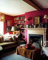 Deep fuchsia pink walls create an atmosphere of comfort and warmth in this intimate living room