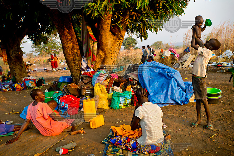 A South Sudanese refugee boy plays with his brother at the spot among trees where his family are camped out in the Dzaipi transit centre.