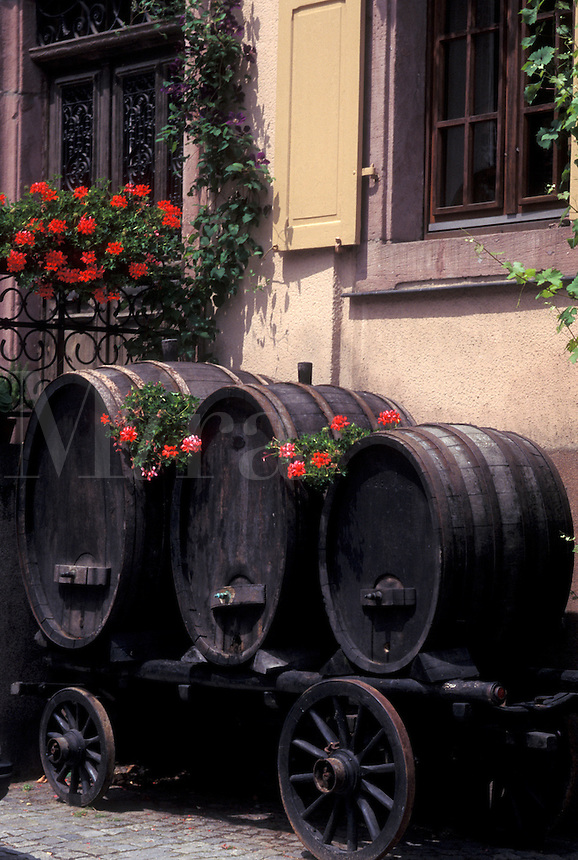 France, Alsace, Kaysersberg, Haut-Rhin, Europe, wine region, Old wooden wine barrels decorated with red geraniums on a wooden wagon in the village of Kaysersberg in the wine region of Alsace.