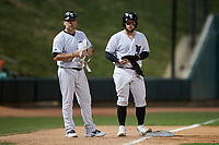 Winston-Salem Dash manager Ryan Newman (left) holds the protective gear of Evan Skoug (9) during the game against the Greensboro Grasshoppers at Truist Stadium on June 15, 2021 in Winston-Salem, North Carolina. (Brian Westerholt/Four Seam Images)