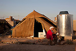 DOMIZ, IRAQ: A woman cleans dishes in the Domiz refugee camp...Over 7,000 Syrian Kurds have fled the violence in Syria and are living in the Domiz refugee camp in the semi-autonomous region of Iraqi Kurdistan...Photo by Ali Arkady/Metrography