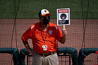Baltimore Orioles usher holding a face mask required sign during a Major League Spring Training game against the Philadelphia Phillies on March 12, 2021 at the Ed Smith Stadium in Sarasota, Florida.  (Mike Janes/Four Seam Images)
