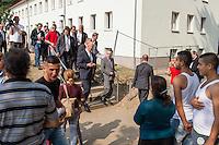 Zentrale Auslaenderbehoerde und BAMF-Aussenstelle in Eisenhuettenstadt.<br /> Bundesinnenminister Thomas de Maiziere und brandeburgs Ministerpraesident Dietmar Woidke besuchten am Donnerstag den 13. August 2015 die Zentrale Auslaenderbehoerde und BAMF-Aussenstelle in Eisenhuettenstadt. Sie liessen sich von Mitarbeitern die Situation in der Einrichtung zeigen und erklaeren, sprachen mit Fluechtlingen und besichtigten das auf dem Gelaende befindliche Abschiebegefaengnis.<br /> Der Besuch des Bundesinnenministers und des Ministerpraesidenten wurde von etwa 40 Journalisten begleitet.<br /> Im Bild: Fluechtlinge vom Balkan betrachten Ministerpraesident Woidke, Links, Bundesinnenminister de Maiziere, rechts und den Pressetross bei ihrem Rundgang.<br /> 13.8.2015, Eisenhuettenstadt/Brandenburg<br /> Copyright: Christian-Ditsch.de<br /> [Inhaltsveraendernde Manipulation des Fotos nur nach ausdruecklicher Genehmigung des Fotografen. Vereinbarungen ueber Abtretung von Persoenlichkeitsrechten/Model Release der abgebildeten Person/Personen liegen nicht vor. NO MODEL RELEASE! Nur fuer Redaktionelle Zwecke. Don't publish without copyright Christian-Ditsch.de, Veroeffentlichung nur mit Fotografennennung, sowie gegen Honorar, MwSt. und Beleg. Konto: I N G - D i B a, IBAN DE58500105175400192269, BIC INGDDEFFXXX, Kontakt: post@christian-ditsch.de<br /> Bei der Bearbeitung der Dateiinformationen darf die Urheberkennzeichnung in den EXIF- und  IPTC-Daten nicht entfernt werden, diese sind in digitalen Medien nach §95c UrhG rechtlich geschuetzt. Der Urhebervermerk wird gemaess §13 UrhG verlangt.]