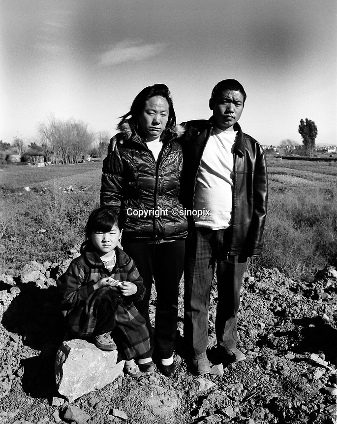 Mr Huang He, poses with his wife and and his daughter, one of their three children, on the suberbs of Kunming. Both parenst were sterilized by force in their remote farming village in Guizhou, Huang He did not receive an anaesthetic.