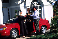 Mom and dad giving daughter graduate keys to her new car as a reward for success in schoo