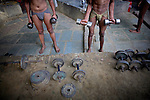 Indian men practice traditional Kushti wrestling on Monday, June 01, 2009 in New Delhi, India. Kushti, India's indigenous form of wrestling, has gone from a royal national sport to a dying art in Asia over the past century.  Those who still practice it meet the lengthy hours of its daily regimen with unrelenting devotion — rope, aerobic and weight exercises; culturing the soil on which they wrestle; a diet comprised of non-spicy, self-made food; and celibacy.  And so, in traditional earthen pits wrestlers still apply the physical and mental intensity that has driven their ancestors for three thousand years.  But a 2004 decision by the Indian Fighters Federation from the capital of Delhi, prohibiting fighting on red soil and ordering fight clubs to use mattresses instead, exacerbated Kushti's diminishing role in Indian tradition.  The order was in part an effort to gather more Olympic medals -- the first by Khashaba Dadasaheb Jadhav, a bronze in 1952, and most recently, also a bronze at the 2008 Beijing Olympics, by Sushil Kumar.