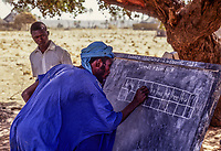 Niger, Doutouel Village, West Africa.  Man Practicing Writing in Adult Literacy Class.