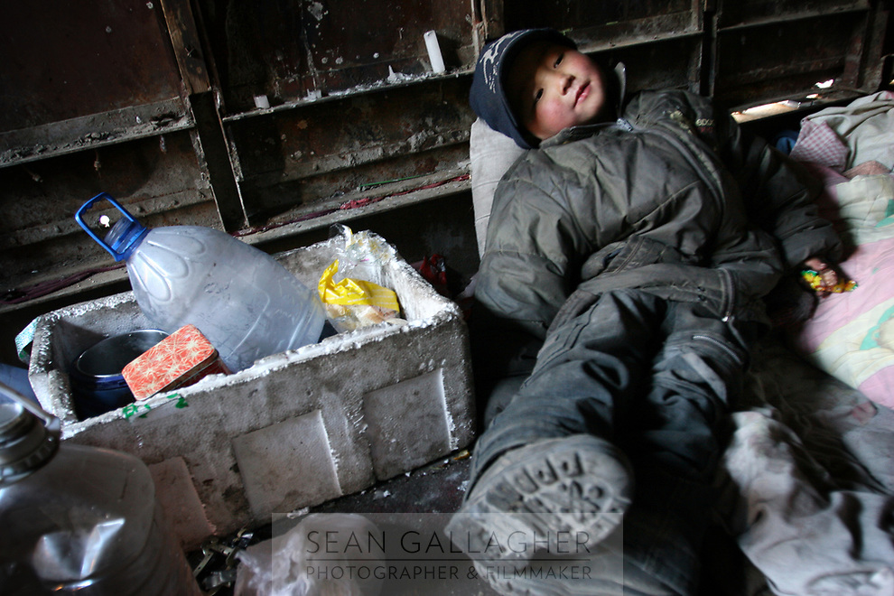 """MONGOLIA. Ulaan Baatar. Huyga takes a rest in the family's garage-home. The family worry most about the future of their child. Street people suffer discrimination  and social stigma from many areas of societyand find it almost impossible to find jobs. Huyga's future is uncertain but on asking what he wanted to be when he was older he revealed; """"I want to be a lama [buddhist monk]. The life is good and I can get a lot of food"""".<br /> As the global financial crisis grips Asia, Mongolia is feeling the implications first hand as the country suffers from rising inflation pushing the price of food and fuel ever upwards. For the country's homeless, who live in sewers and abandoned garages in the capital and already face extreme discrimination and are denied access to basic health and social care, their lives are hanging in the balance. 2008"""