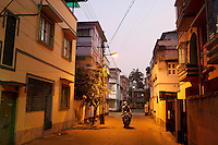A motorbike drives through a residential district at dusk in Kolkata.<br />