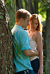 Young couple embracing, leaning against tree