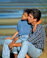 Father and daughter relax in the dune grass by the beach, Cape Cod