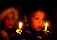 A young boy holds a glowing candle during a Christmas service with is Cub Scout pack.